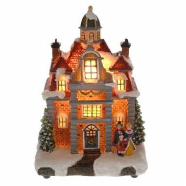 Kersthuisje met gezin met verlichting