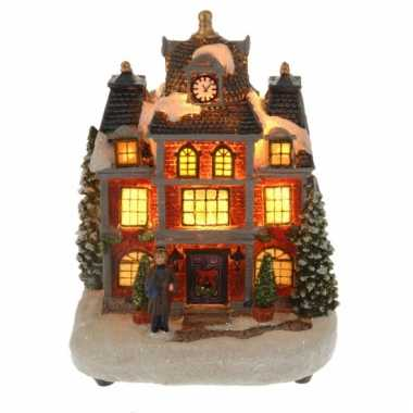 Kersthuisje met man met verlichting
